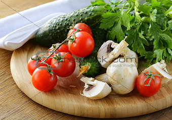 tomatoes, cucumbers, mushrooms and parsley on a cutting board