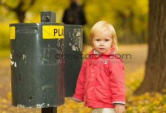 Portrait of baby near trash can