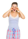 Young woman in pajamas rubbing eyes