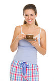 Happy young woman in pajamas after sleep with cup of coffee