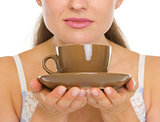 Closeup on cup of coffee in woman hands