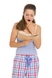 Young woman reading book before sleep and yawing