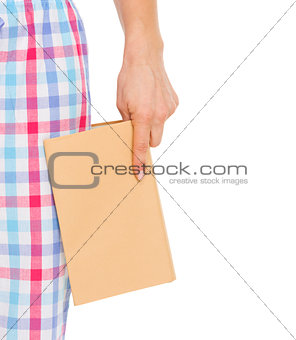 Closeup on book in woman hand near leg in pajamas pants