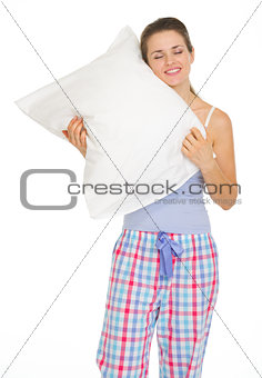 Young woman in pajamas enjoying cosy pillow