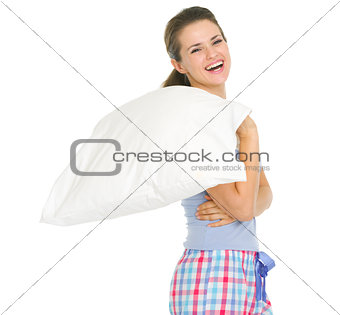Smiling young woman in pajamas holding pillow