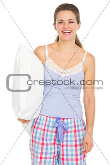 Happy young woman in pajamas holding pillow