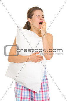Happy young woman in pajamas with pillow yawing