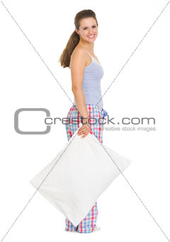 Full length portrait of young woman in pajamas with pillow