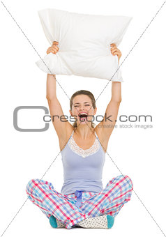 Cheerful young woman in pajamas sitting and holding pillow