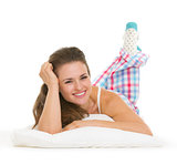 Smiling young woman in pajamas laying on pillow isolated on whit