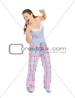 Full length portrait of young woman in pajamas singing in microp