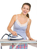 Young woman in pajamas ironing