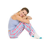 Happy young woman in pajamas sitting on floor isolated on white