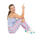 Smiling young woman in pajamas sitting on floor and pointing on 