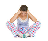Stressed young woman in pajamas sitting on floor