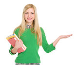 Smiling student girl with books showing something on palm