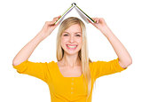 Smiling student girl making roof with book