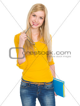 Portrait of happy student girl with book and glasses