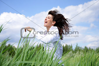 Woman with long hair running outside under blue sky in the field