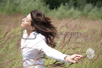 Beautiful woman outside, with wind in her face and a flower in h