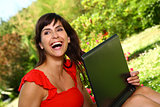 Happy woman with a computer laughing outside in the sunshine.
