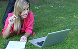 Young student outside in the park with  computer and notebook st