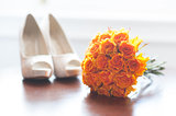 wedding shoes and bouquet of orange roses