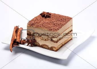 Tiramisu cake with cherries on a white plate