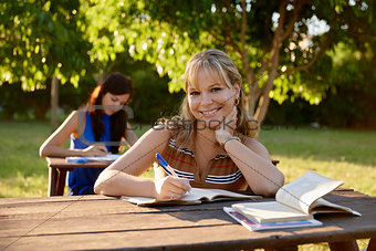 Young women studying with textbook for college exams at school