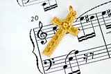 A golden cross on the top of a music sheet concept of religion