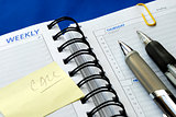Write some notes on the day planner isolated on blue