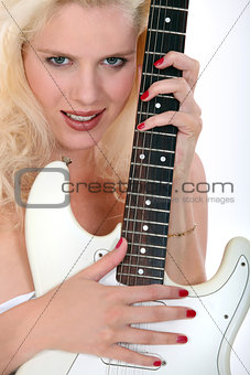 Blond woman holding electric guitar