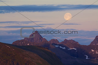 Moon above rocky peaks
