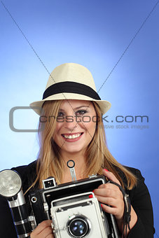 Blond woman pointing an old camera