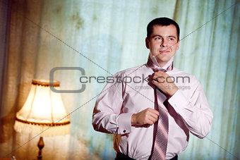 handsome man putting on a necktie