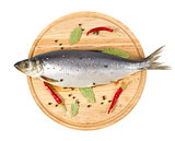 herring with spice on wooden plate