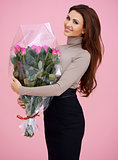 Happy brown haired young woman holding flowers
