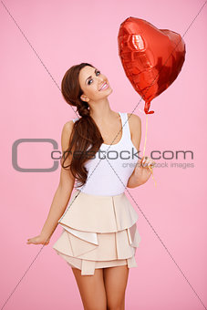 Vivacious sexy woman with heart balloon