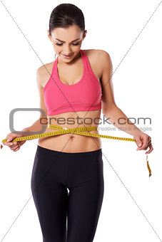 Female athlete measuring her waist
