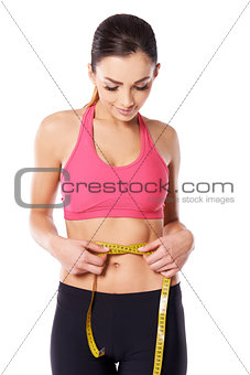 Young athlete measuring her waist
