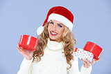Smiling woman in Santa hat holding Christmas gifts