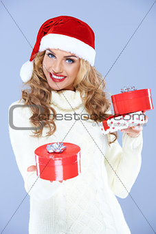 Pretty woman in Santa hat holding Christmas gifts