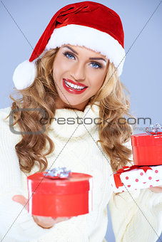 Close up of woman in Santa hat holding Christmas gifts
