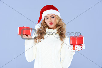 Sexy woman in Santa hat trying to decide which gift