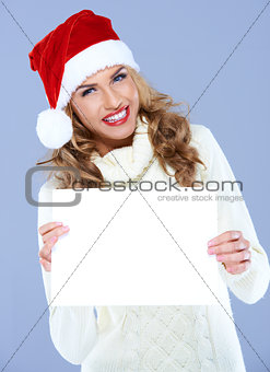 Smiling woman in Santa hat holding blank board