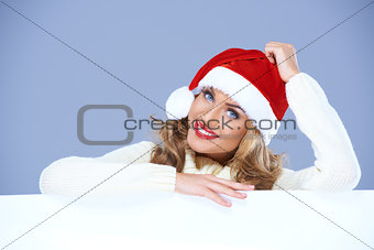 Woman in a santa hat resting on a blank billboard