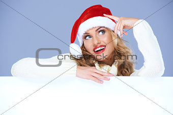 Blond woman in Santa Hat resting on white board