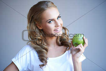 Head shot of woman holding green apple against grey