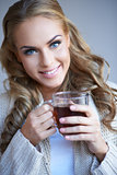 Closeup portrait of a pretty woman holding a cup of tea