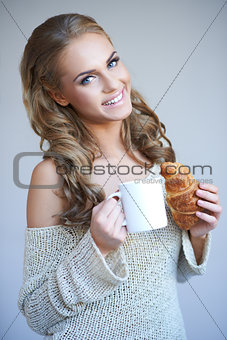 Cute girl holding white cup of hot drink while isolated